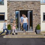 Outside a house, woman and man walking out of glass doors and young boy and girl walking up the steps towards them.