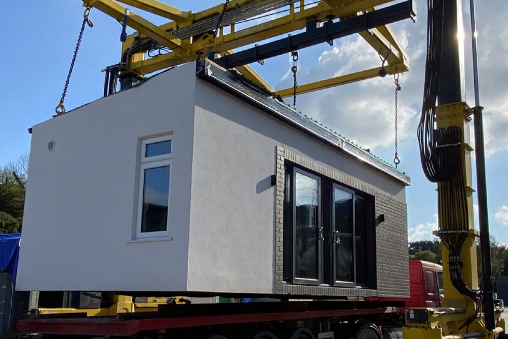 Plaster white garden room being placed onto a red truck by a yellow crane.
