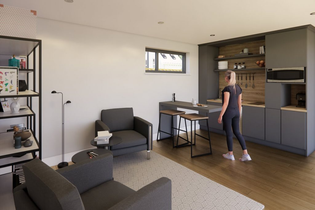 Inside NUA 45 garden room, with black utilities walls and breakfast bar table and two stools. Two black grey seats. Woman standing at the breakfast bar.