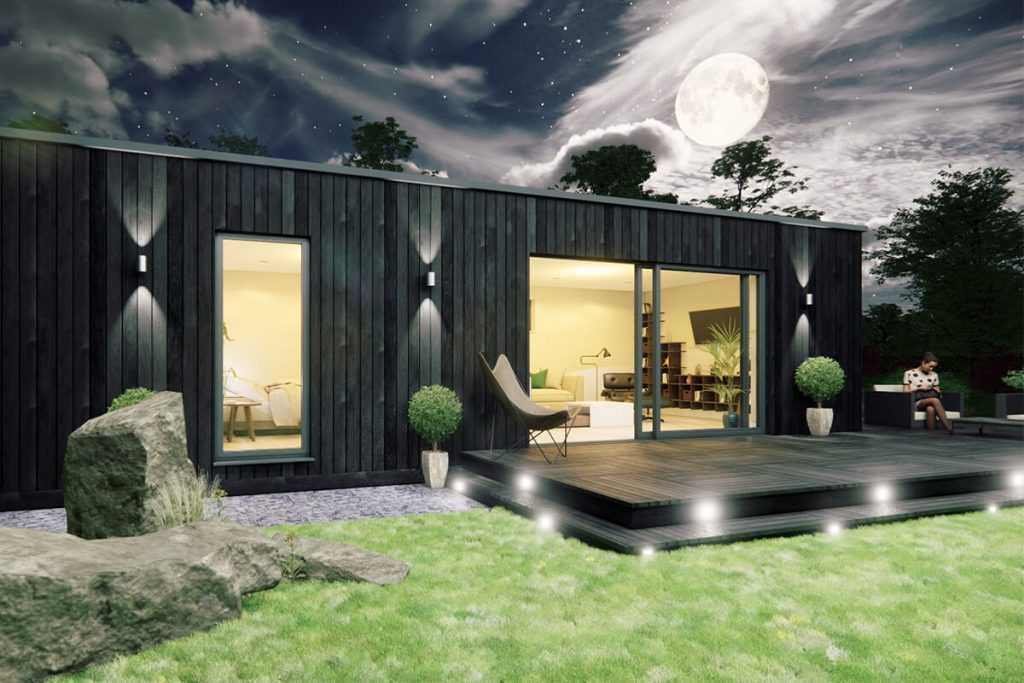 Charred wood garden room with charred wood patio. At night time with lights on.